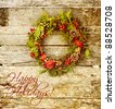 "Christmas card design featuring  a home made christmas wreath with natural decorations hanging on a rustic wooden wall with text ""Merry Christmas."" - stock photo"