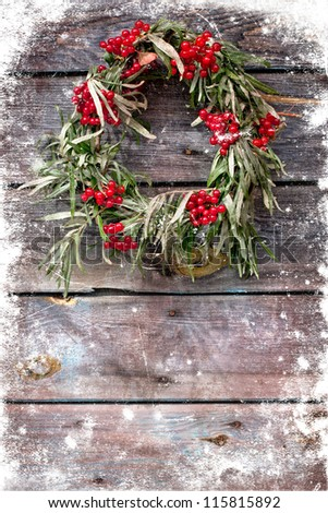 Christmas card design featuring a home made christmas wreath with natural decorations hanging on a rustic wooden wall /holidays background - stock photo