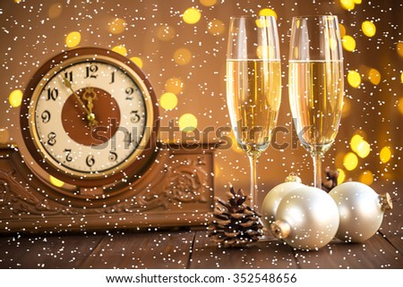 Christmas card. Glasses of champagne on New Year's Eve on the stand an ancient clock with snow