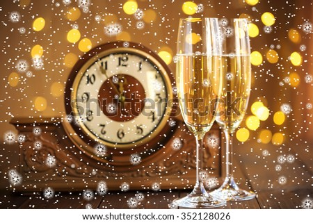 Christmas card. Glasses of champagne on New Year's Eve on the stand an ancient clock with snow and stars