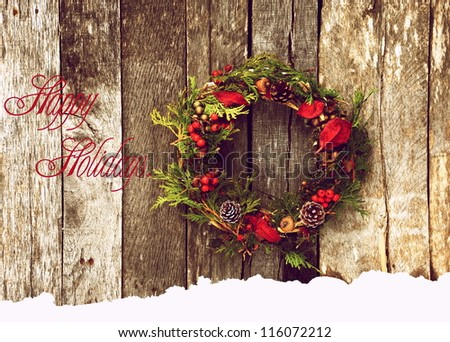 "Christmas card  with a Christmas wreath hanging on a rustic wooden wall with text ""Happy Holidays!"" - stock photo"