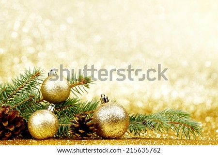 Christmas card with fir tree branch and decoration on golden glitter background - stock photo