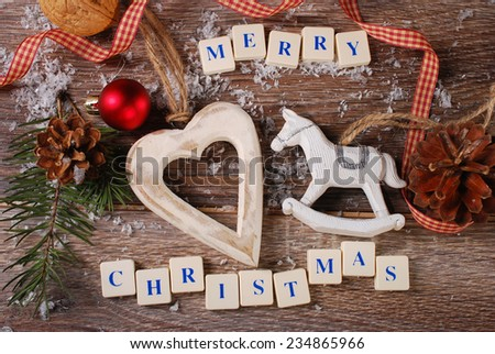 christmas card with greetings made of  letter cubes with vintage rocking horse and heart on wooden background - stock photo