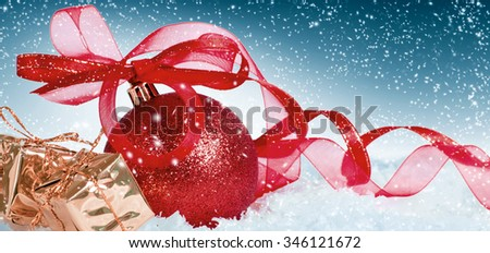 Christmas card with red ball with bow and gift boxes on the snow. Merry Christmas inscription  - stock photo