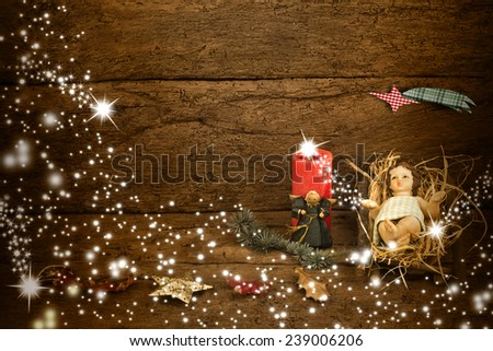Christmas card with space for message, the Child Jesus in his crib on old wooden background and Christmas decorations - stock photo