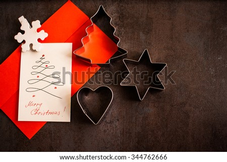 Christmas card with star, heart and pine tree shaped cookie cutters on a dark background - stock photo