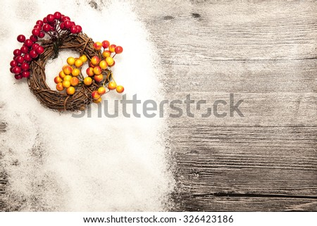 Christmas card with winter snow and christmas wreath with red and yellow rowan berries on wooden background. - stock photo