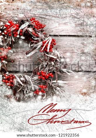 Christmas card with wreath with natural decorations hanging on a rustic wooden wall with copy space with a snow/holidays background - stock photo