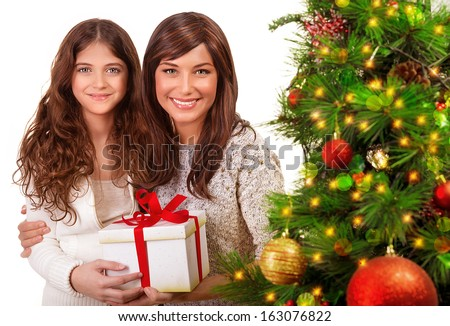 Christmas celebration at home, young mother with daughter having fun near beautiful decorated Xmas tree, receive present, happy holidays concept - stock photo