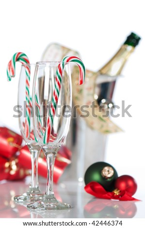 Christmas champagne glasses with candy canes and bottle in ice bucket in background - stock photo