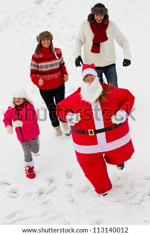 Christmas - Chasing Santa Claus - happy family enjoying Christmas - stock photo