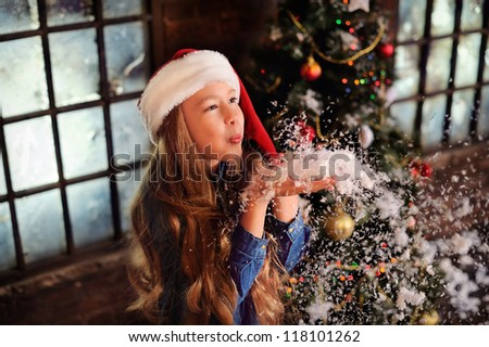 Christmas. Child blowing the snow. In the background, the large windows and the Christmas tree with ornaments. Sorcery and magic. A girl with long hair. - stock photo
