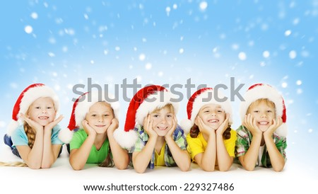 Christmas Children In Santa Helper Hat, Little Kids Boys and Girls Happy Greeting Xmas Holiday, lying over blue background - stock photo