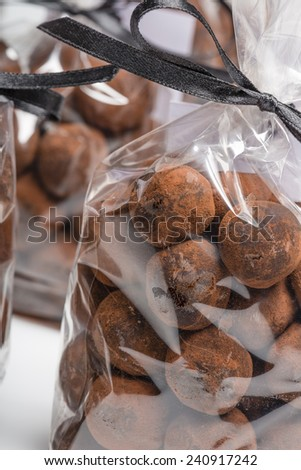 Christmas chocolate truffles in luxury plastic bags with black ribbon. Closeup of gifts. Shooting on white background in studio. - stock photo