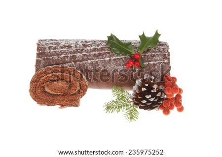 Christmas chocolate yule log decorated with seasonal foliage with a slice cut, isolated against white - stock photo