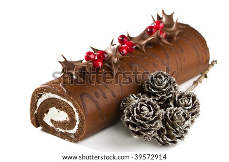 Christmas chocolate yule log with holly, berries, and pine cones