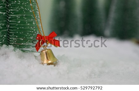 Christmas. Christmas bell with a red ribbon and a background filled with snow and tree.