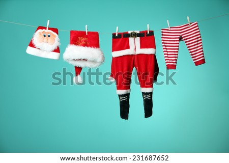 Christmas clothes hangs on a rope isolate on green background  - stock photo