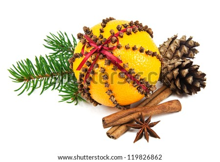Christmas clove and orange pomander with spices, pine cones and spruce branch on white - stock photo