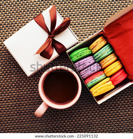 Christmas coffee break with gift box and macaroons with a retro vintage instagram filter.