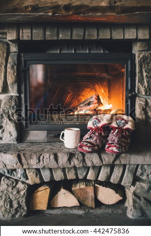 Christmas comfortable slippers by the warm cozy fireplace. Relaxing atmosphere in a chalet by authentic vintage fireside with a cup of hot drink. Winter and Christmas holidays concept