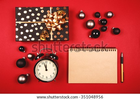 Christmas coming concept. Present, toys, alarm clock and clean notebook with pen are lying on the table, on the red background. Place for writing goals or new year wishes. - stock photo