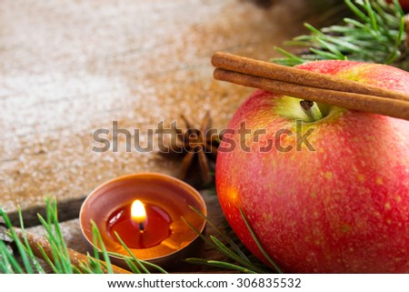 Christmas composition: apple candle and cinnamon stick. Selective focus, copy space background - stock photo
