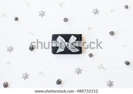Christmas composition. Christmas gift, snowflakes, pine cones and gypsophila flowers. Flat lay, top view