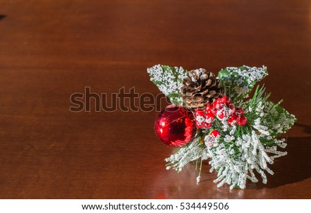 Christmas composition made up of a pine cone open, from red berries, with red ball and white flowers.
