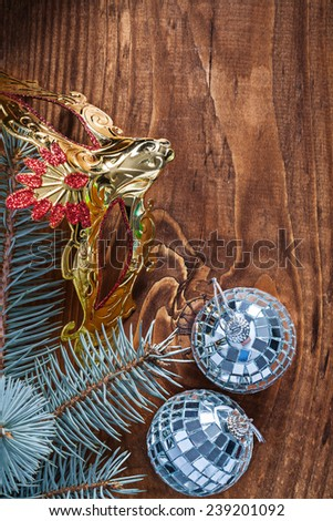 christmas composition mirror disco balls and pinetree branch with golden carnaval mask on old wooden board - stock photo