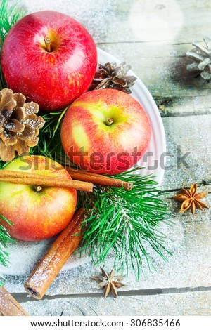 Christmas composition on a platter: apples, tree branches, cinnamon sticks. Snowing.  - stock photo