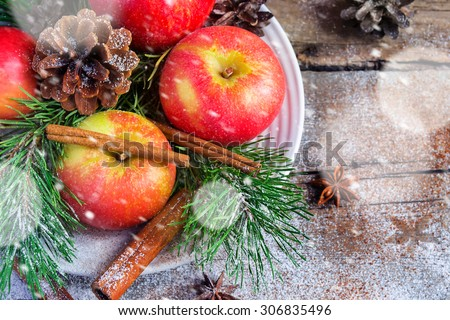 Christmas composition on a platter: apples, tree branches, cinnamon sticks. Snowing.