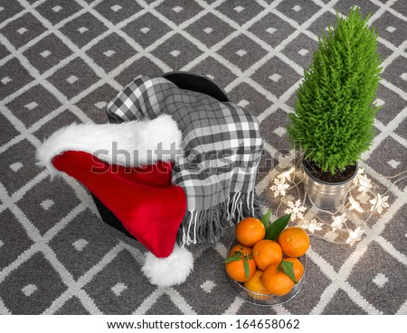 Christmas composition. Santa hat, lights, checked plaid, clementines, and little green tree. - stock photo