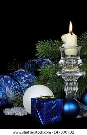 Christmas composition with a burning candle on a black background - stock photo