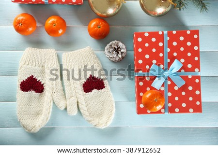 Christmas composition with a gift box, mittens and decorations on a blue table