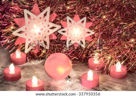 Christmas composition with ball, stars and candles close up on a festive background of tinsel. Photo toned in pink. Selective focus - stock photo