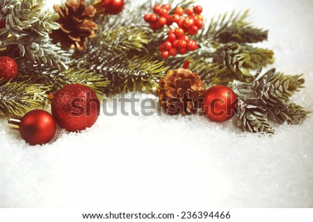 Christmas composition with baubles and fir-tree on snow close-up