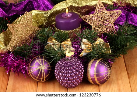 Christmas composition  with candles and decorations in purple and gold colors on wooden background - stock photo