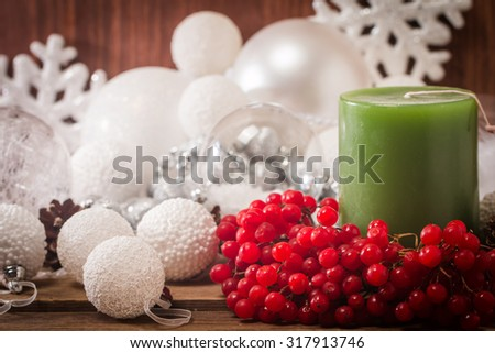 Christmas composition with candles and viburnum on wooden background - stock photo