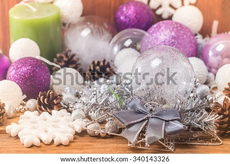 Christmas Composition with Gifts and candle, white balls, pine cones, snowflakes on wooden table. Toned. - stock photo