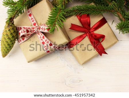 Christmas composition with very great branches of conifer on white wooden background and cute small gift box wrapped with simple brown craft paper and decorated with ribbon. Greeting theme. Copy space - stock photo