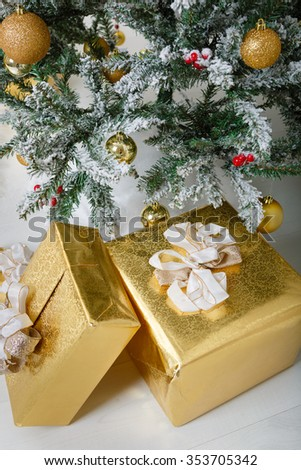 Christmas composition. Xmas tree with gold balls, decorations, toys. White snow on branches. Different size gifts under tree. Gold wrap and pretty bow. Winter holidays card.  - stock photo