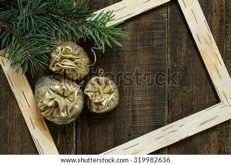 Christmas concept: bags with gifts of gold brocade on the spruce branches in the frame of birch bark - stock photo