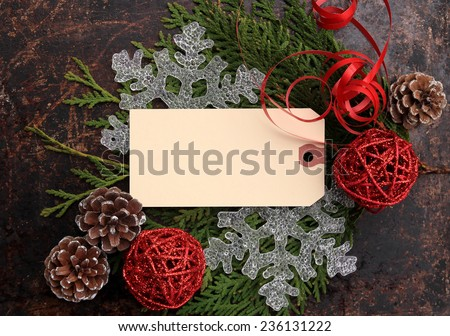 Christmas concept. Fir tree branches, pine cones, snowflakes, red wicker balls and red ribbon on brown rustic background, and tag with copy space. Use you own text. - stock photo
