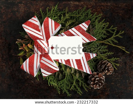 Christmas concept. Fir tree branches, red and white bow, pinecones and blank tag with copy space on brown rustic background. Use your own text. - stock photo