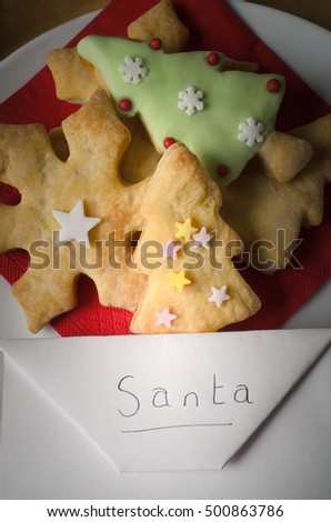 Christmas concept. Overhead of a plate of shaped Christmas biscuits (cookies) with an envelope addressed to Santa.