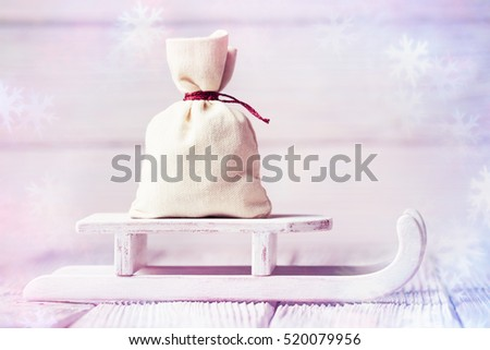 Christmas concept with bag on sledge over blurred wooden background