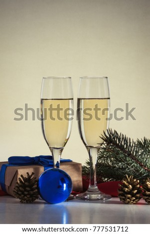 Christmas concept with glasses of champagne and a gift and a blue ball