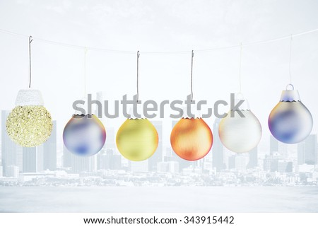 Christmas concept with multicolored balls on the rope - christmas tree toys at city background - stock photo