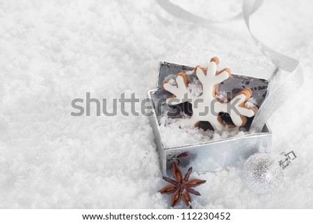 Christmas Cookie in a silver gift box on snowy background with copyspace - stock photo